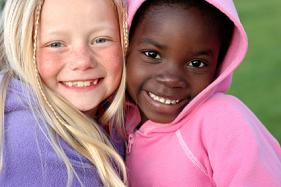 two girls white and black smiling mixed dentition